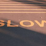 Slow sign on pavement